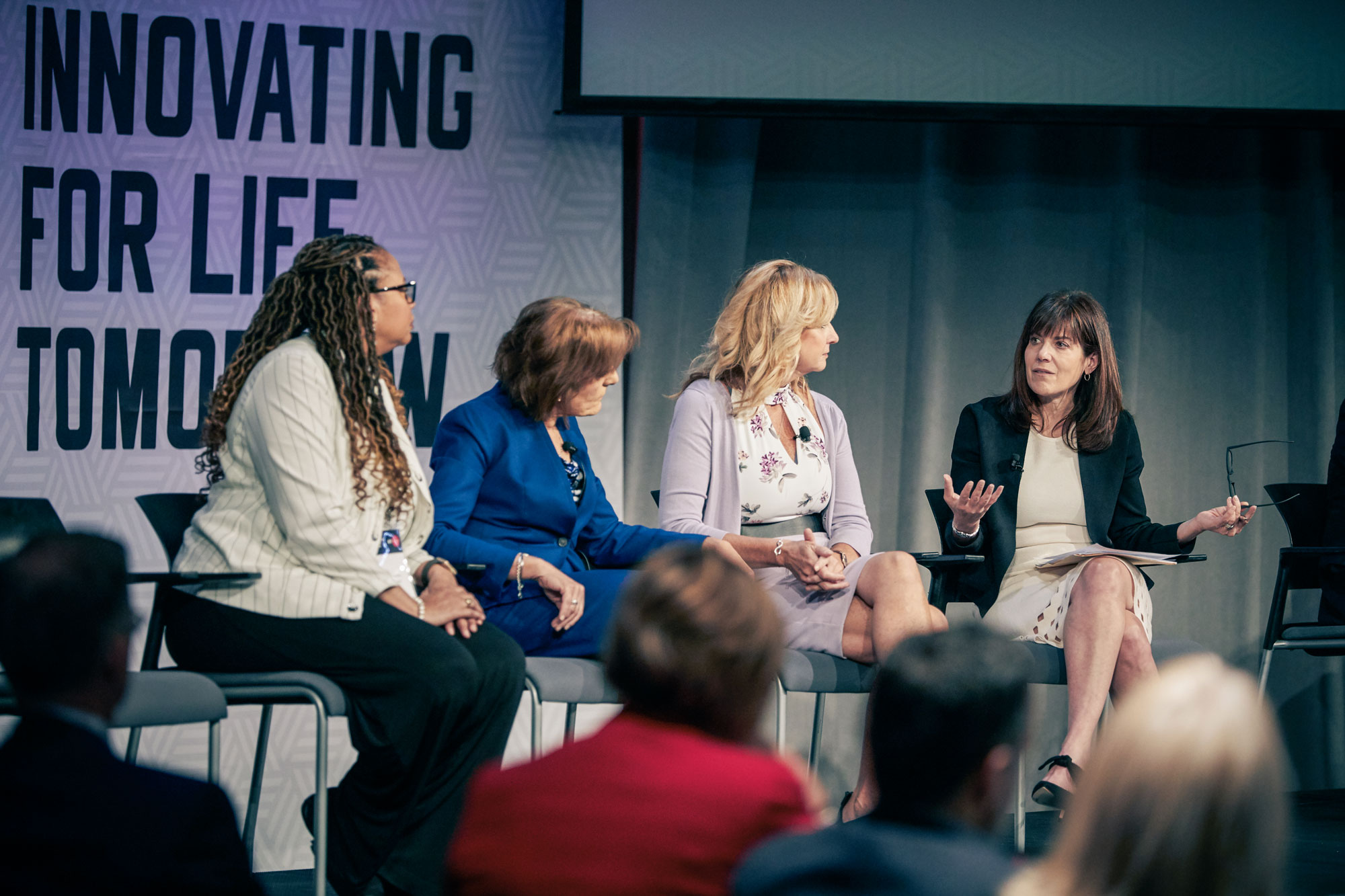 4 women sit in chairs on a stage and one is speaking while the others look toward her